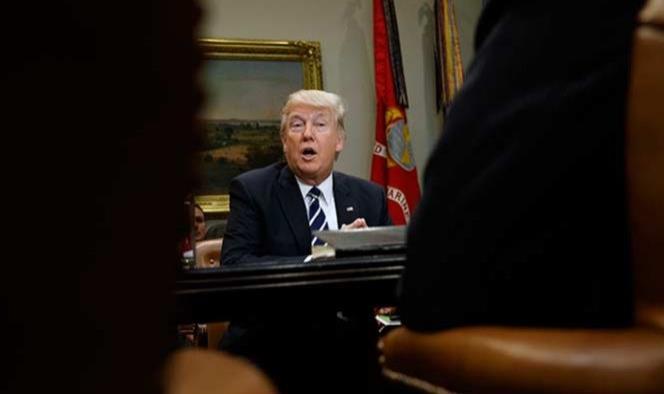 Trump esquiva crisis de asesor y arremete contra la prensa