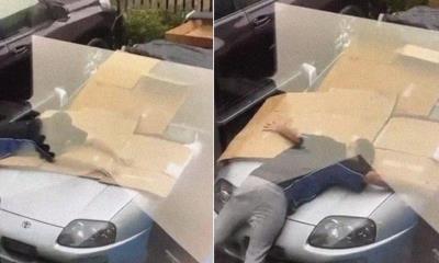 Un joven protege su coche deportivo de una granizada cubriéndolo con su propio cuerpo